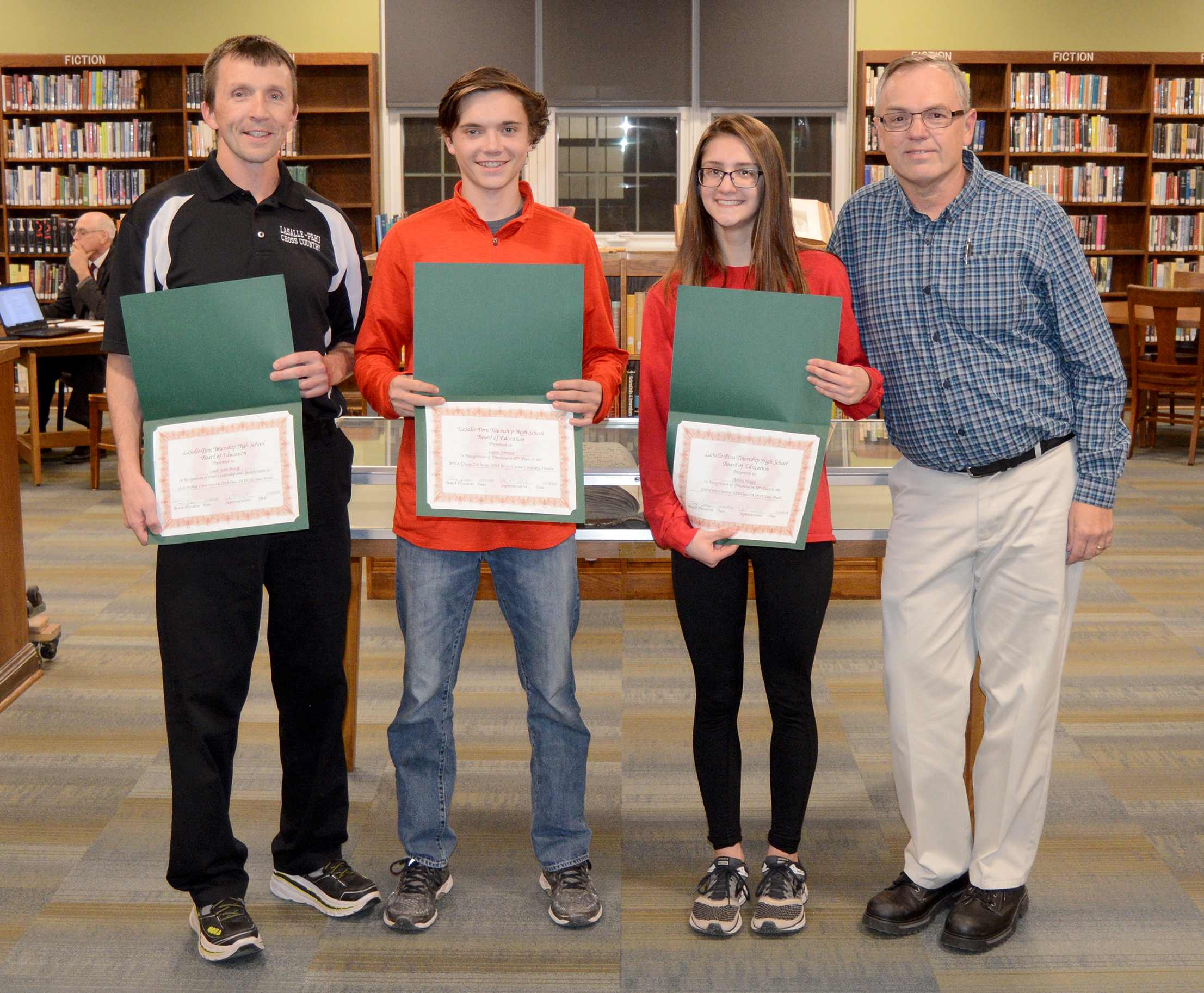 The board Recognized student-athletes and coaches of the state-qualifying cross-country team.