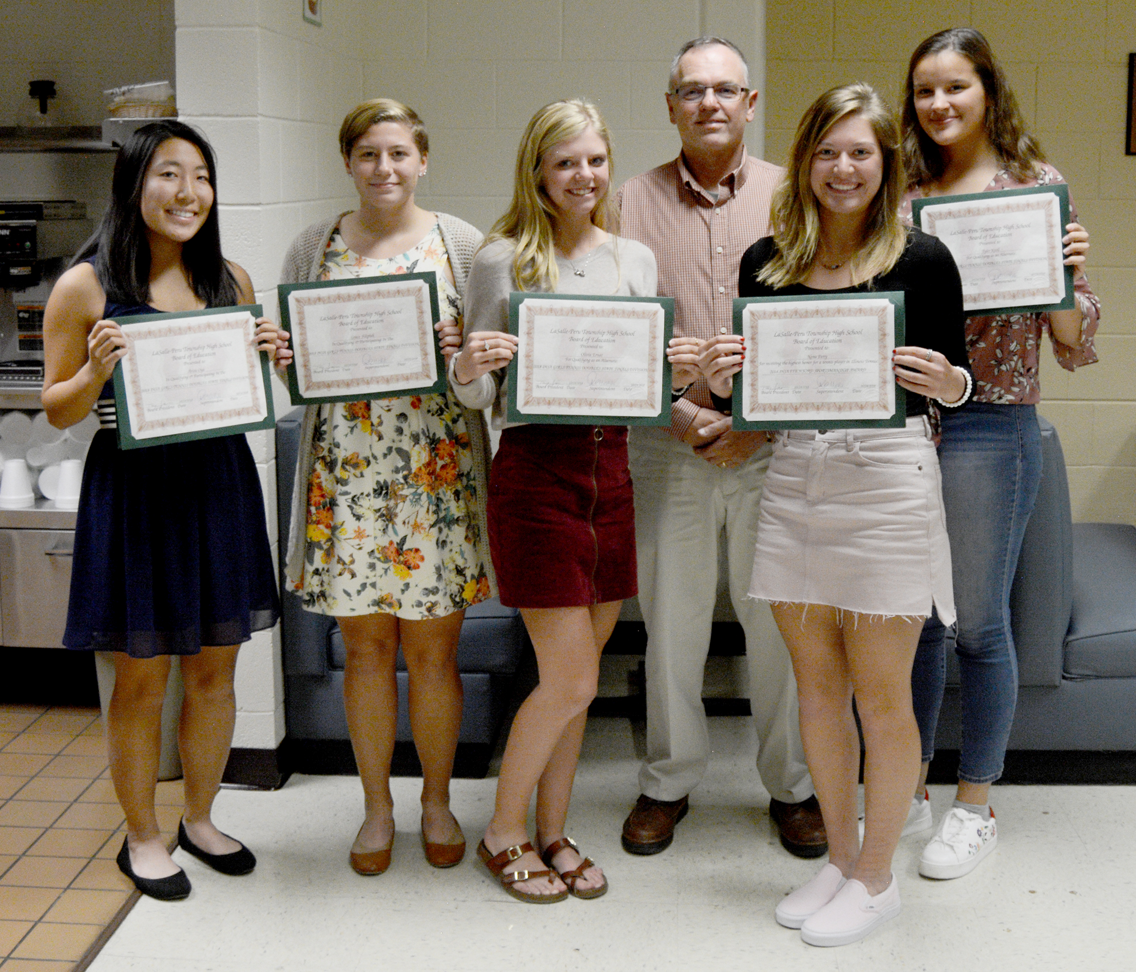 Board President Tony Sparks poses with girls tennis players.