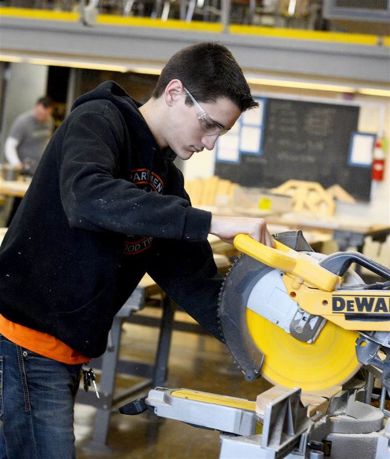 Student working in wood shop with a miter saw.